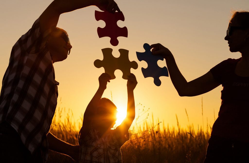 Family at sunset with large puzzle pieces